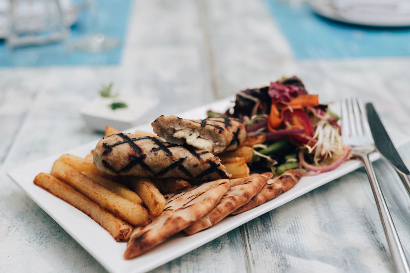 Greek style stuffed chicken kebab Chicken Cuisine Fork Fries Greek Knife Meal Salad Stuffed Close-up Food Food And Drink French Fries Greek Food Kebab No People Pita Bread Plate Ready-to-eat Serving Size Still Life Tzatziki