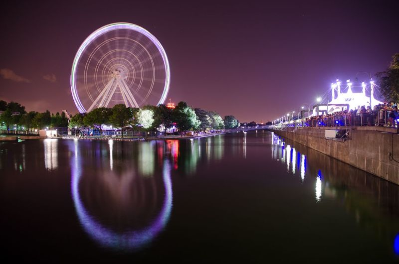 Illuminated ferris wheel by river against sky at night