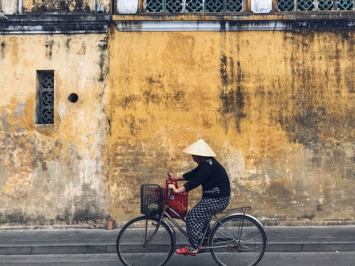 Culture And Tradition Travel Photography Travel Destinations Travel Basket Historical Site Conical Hat Yellow Wall Vietnamese Women Vietnamese Bicycle Real People Transportation Cycling One Person Mode Of Transport Outdoors Full Length Land Vehicle Street Riding City Life Building Exterior City Built Structure Day Architecture Lifestyles One Man Only Adult
