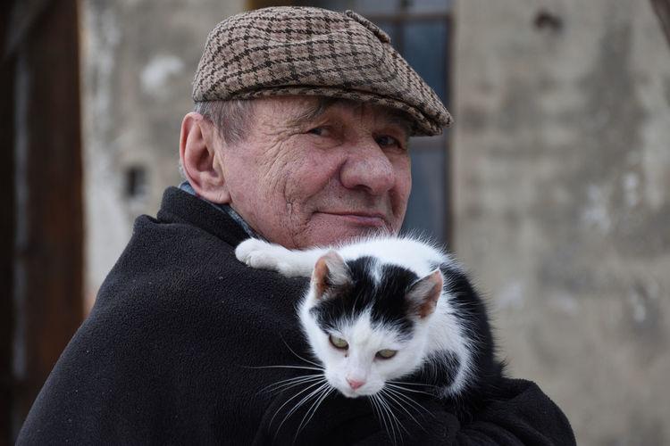 Portrait of senior man carrying cat against house