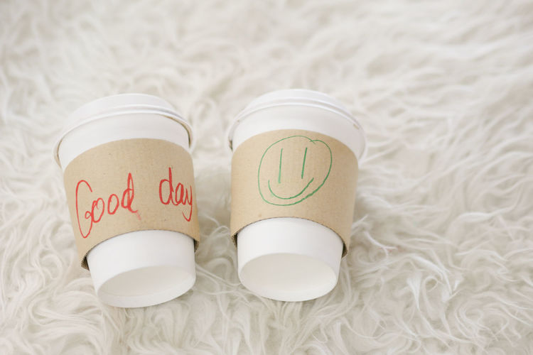 """Two coffee cups with the hand writing word """"Good day"""" and drawing smaile icon on hot cup sleeve with white rug Breakfast Good Day Happy Morning Work Celebration Close-up Coffee Cup Communication Container Day Focus On Foreground Food Food And Drink High Angle View Holiday Indoors  No People Representation Rug Smiling Still Life Text Western Script White Color"""
