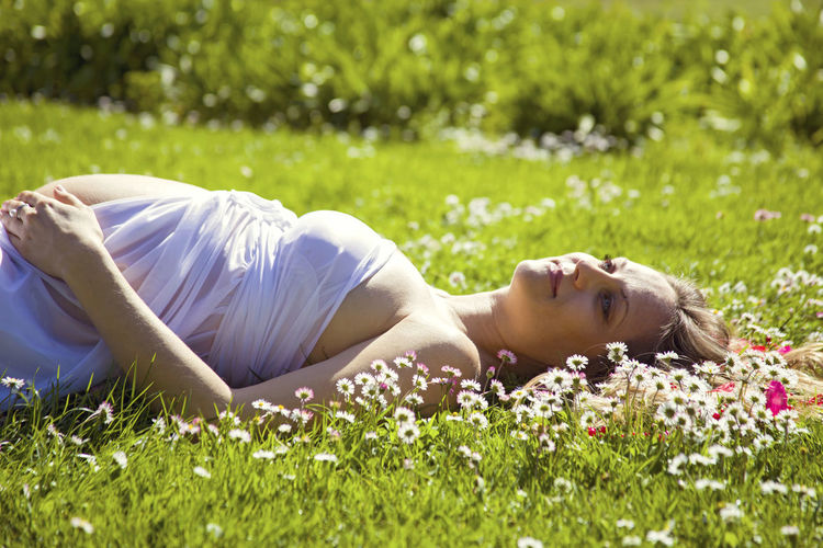 Smiling Pregnant Lying On Grassy Field
