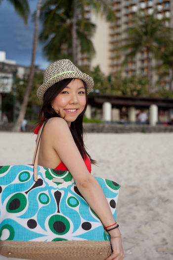 Side view portrait of smiling woman standing at beach