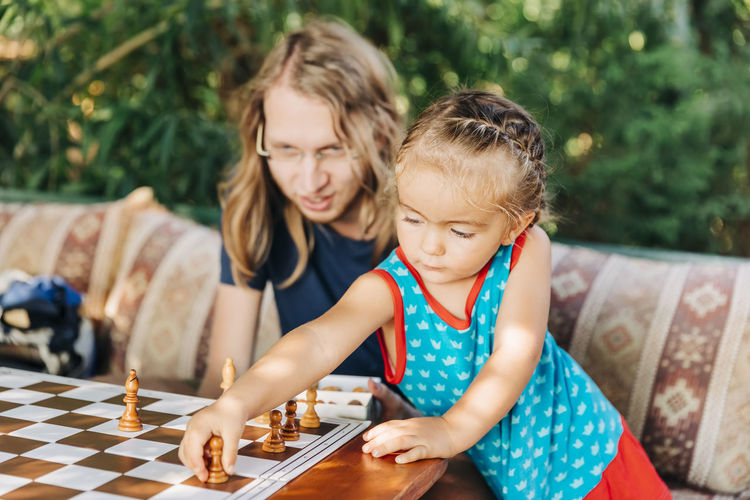 Father teaching chess to daughter while sitting on sofa at home