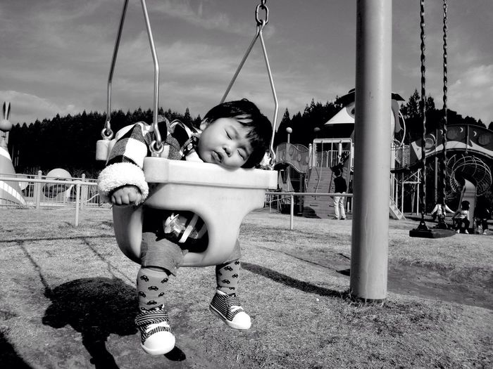 Close-up of baby sleeping on playground swing