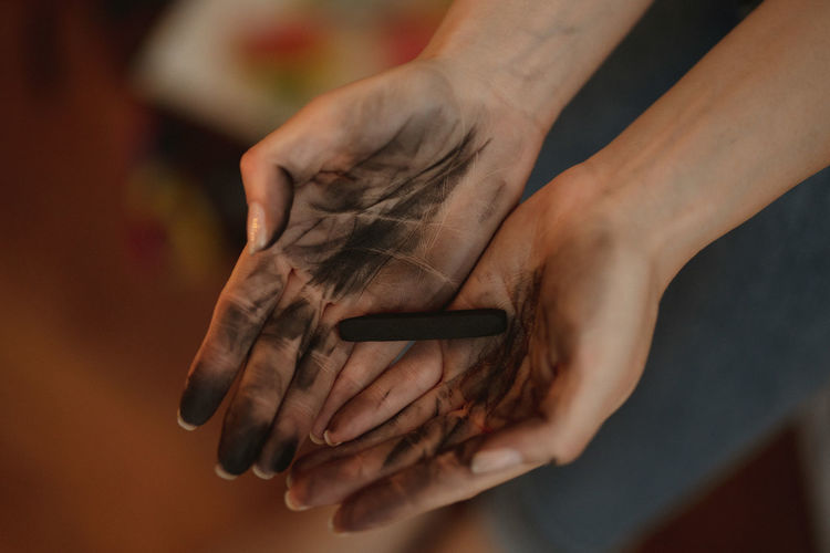 Close-up of hand holding charcoal