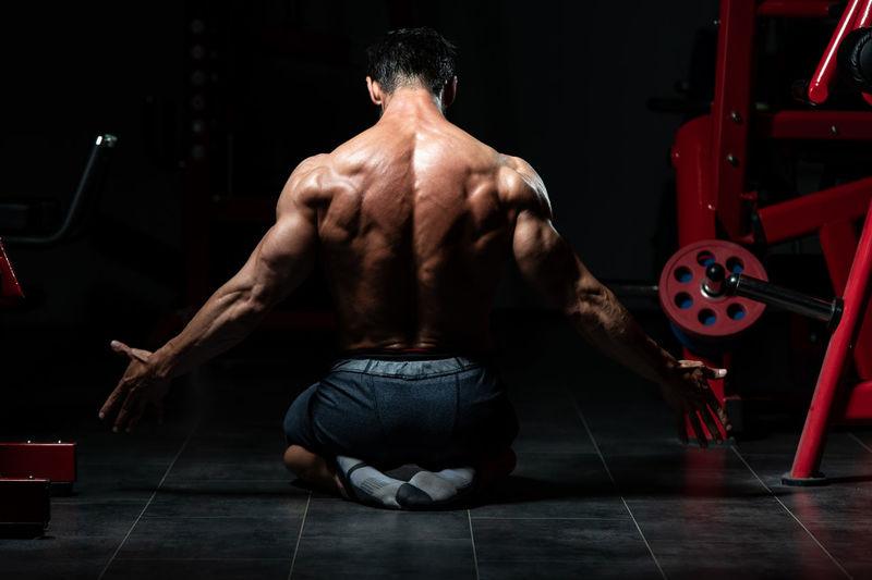 Rear view of shirtless man sitting at home