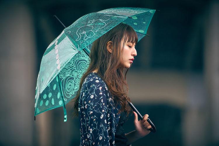 Close-up of wet person holding umbrella
