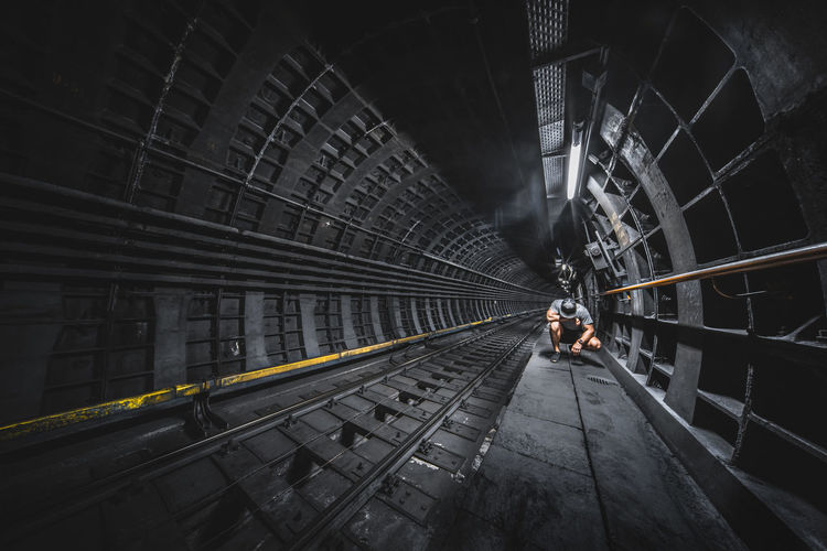 Full length of man crouching in tunnel