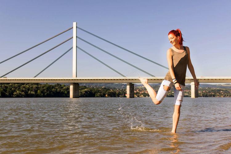 Woman standing on bridge over sea against sky