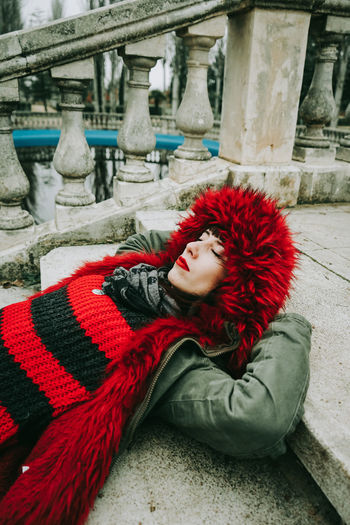 Woman with closed eyes in fur coat lying on staircase