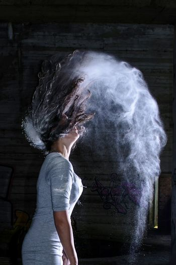 Side view of woman flipping hair in powder
