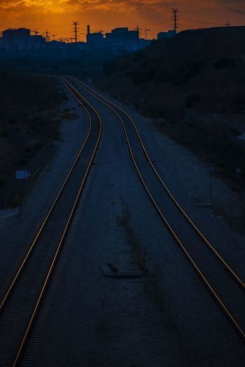 High angle view of railroad tracks by road against sky