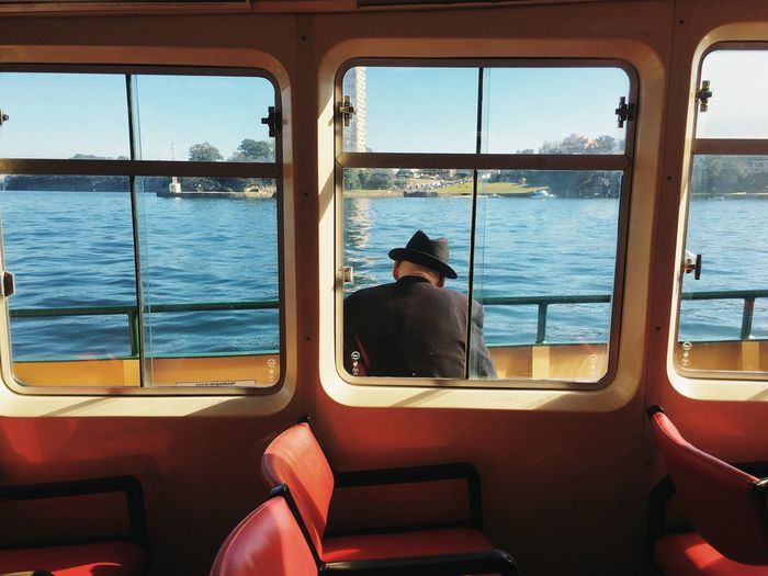 Rear View Of Man Sitting In Ferry Boat