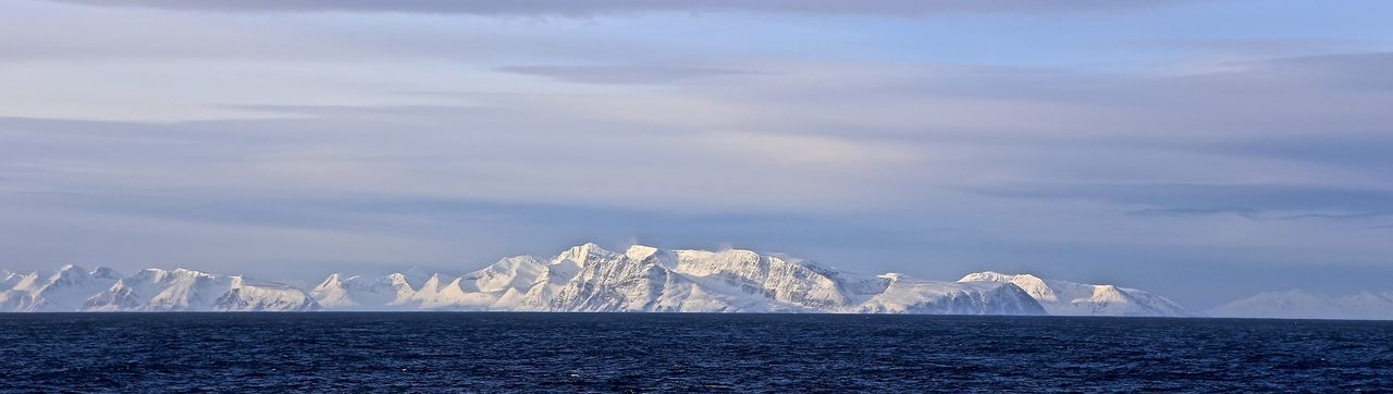 Panoramic view of snowcapped mountains in front of sea against cloudy sky