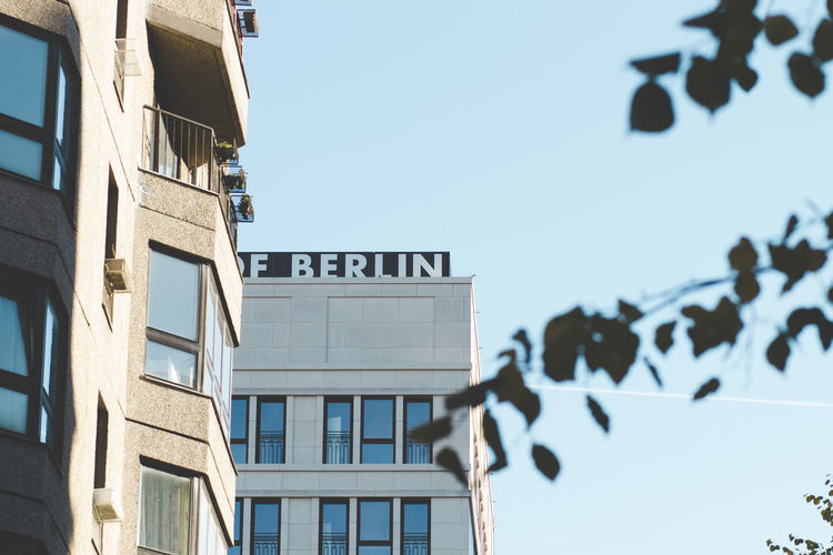 Berlin Building Exterior Built Structure Architecture Sky Building Low Angle View Day Text Nature No People Communication Clear Sky Sign City Outdoors Window Western Script Sunlight Focus On Foreground Information