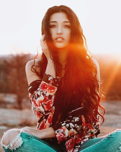 Portrait Of Young Woman Sitting On Field During Sunset