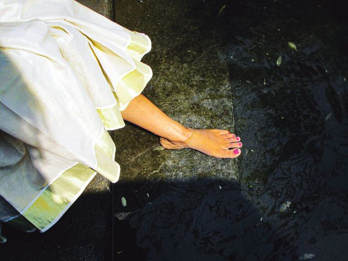Low section of woman standing by water