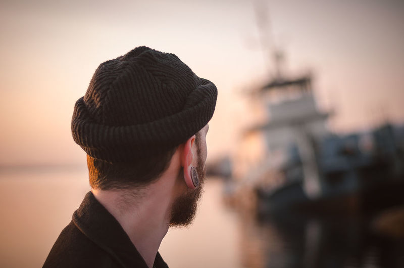 Close-up of man wearing knit hat against sky during sunset
