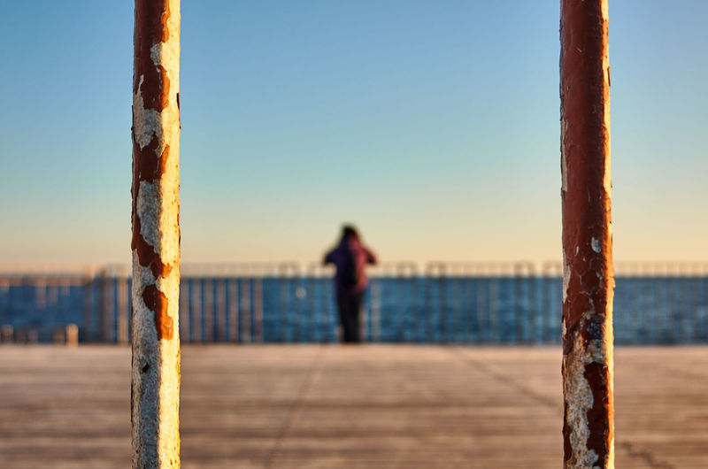 Rear view of woman standing on rusted metal post and boardwalk at sea shore against clear sky