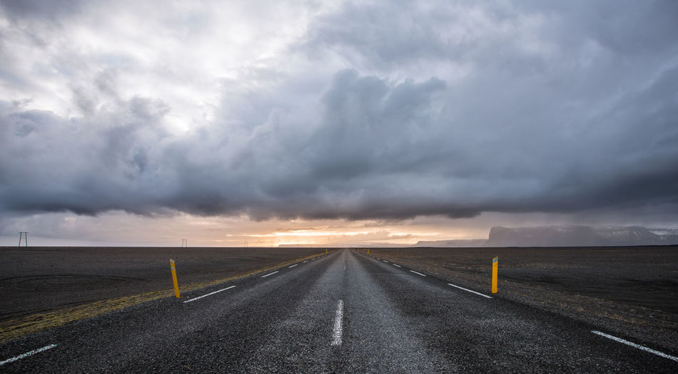 A road leading to distance through black sand landscape with dramatic clouds and mountains in background. Iceland Mountain Mountains Travel Destinations Landscape Travel Black Sand Highway Nordic Countries Nature Road Trip Trip Golden Hour Cloudy Beauty In Nature Sunset Storm Cloud Road Dawn Panoramic Rural Scene Sunlight Dramatic Sky Country Road Empty Road Atmospheric Mood Moody Sky vanishing point The Way Forward Romantic Sky Visual Creativity