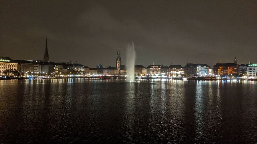 Illuminated buildings at waterfront at night