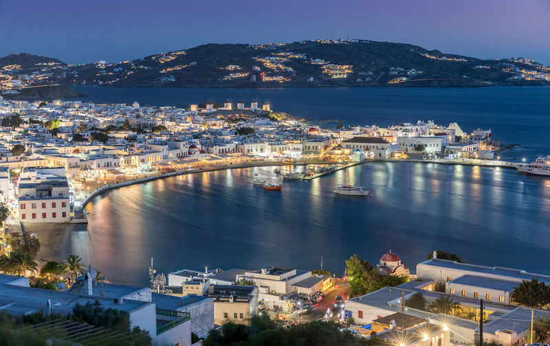 View over the town of Mykonos island in the Cyclades, Greece Aegean Architecture Building Exterior Built Structure Cityscape Evening Greece Greek High Angle View Holiday Illuminated Island Lights Mountain Mykonos Night Outdoors Scenics Sky Summer Tourism Town Travel Destinations Water Windmill