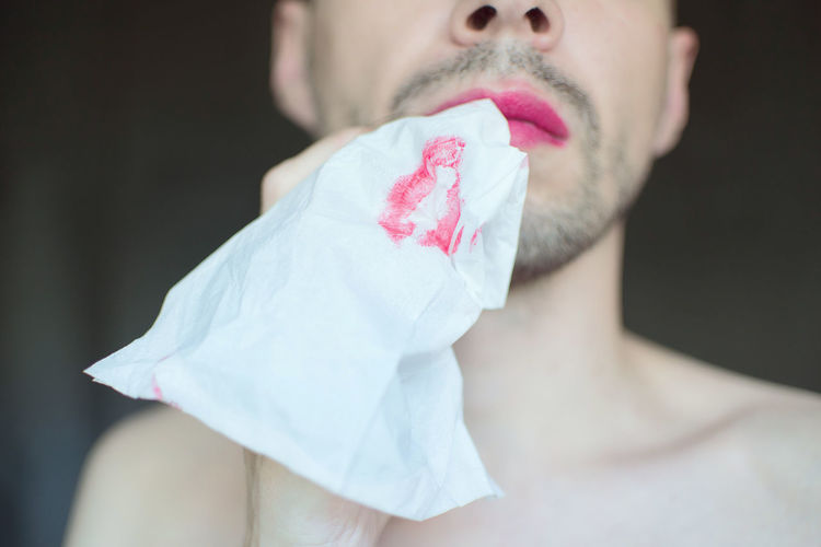 Midsection of transgender man carrying tissue paper with lipstick in mouth