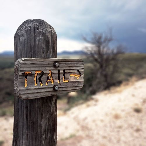 Close-up of sign on wooden post against sky
