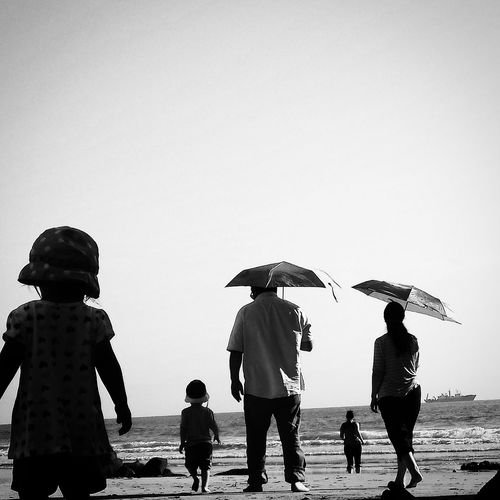 Rear view of family walking on shore against clear sky