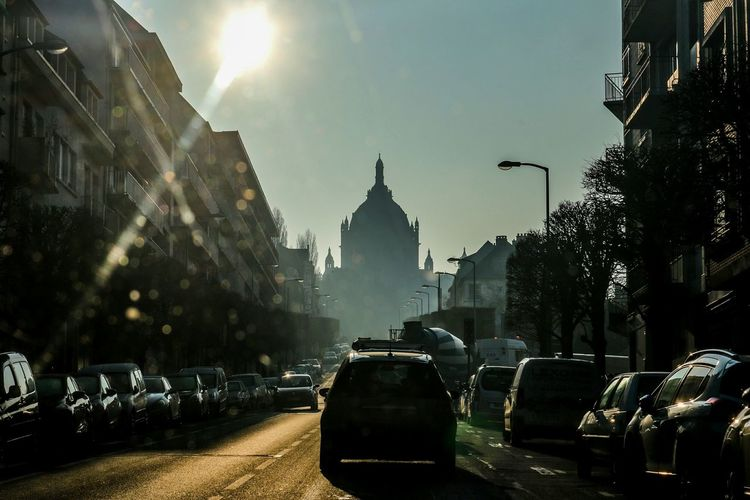 In the distance stands a place of reverence of St Therese of Lisieux. . Bascilica St Therese City City Street Architecture Street Car Outdoors Night Cityscape Travel Destinations Building Exterior Fog