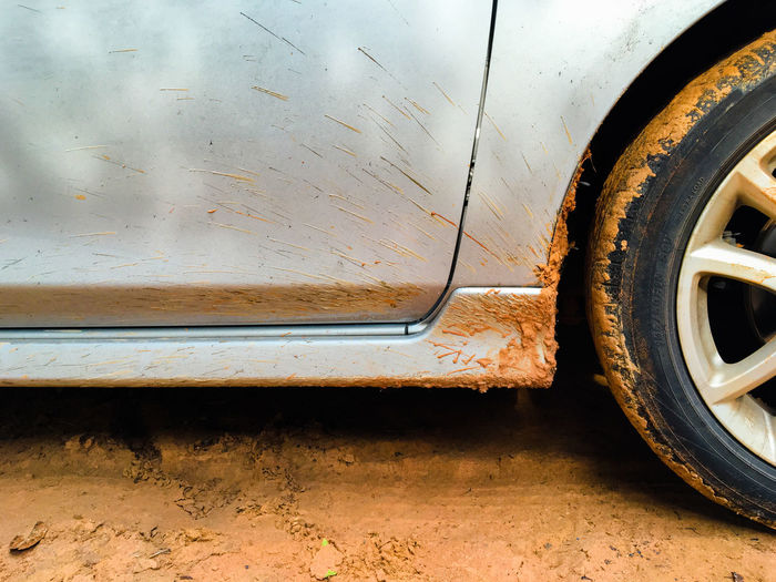 Cropped Image Of Car On Muddy Road