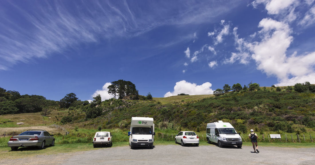 Car park wirh hiker in Hahei, New Zealand. Camping Car Park Cars Hiking Parking Lot Transportation Travel Vacations Camper Campervan Campground Campinglife Car Full Length Medium Group Of Objects New Zealand One Person Parking People Recreational Vehicle Road Trip Rv Stationary Tourism Van