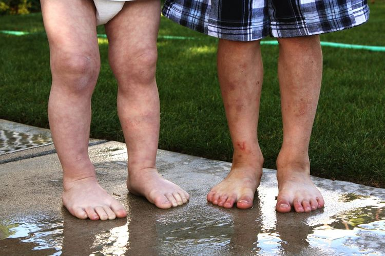 Low Section Of Siblings Standing On Wet Footpath