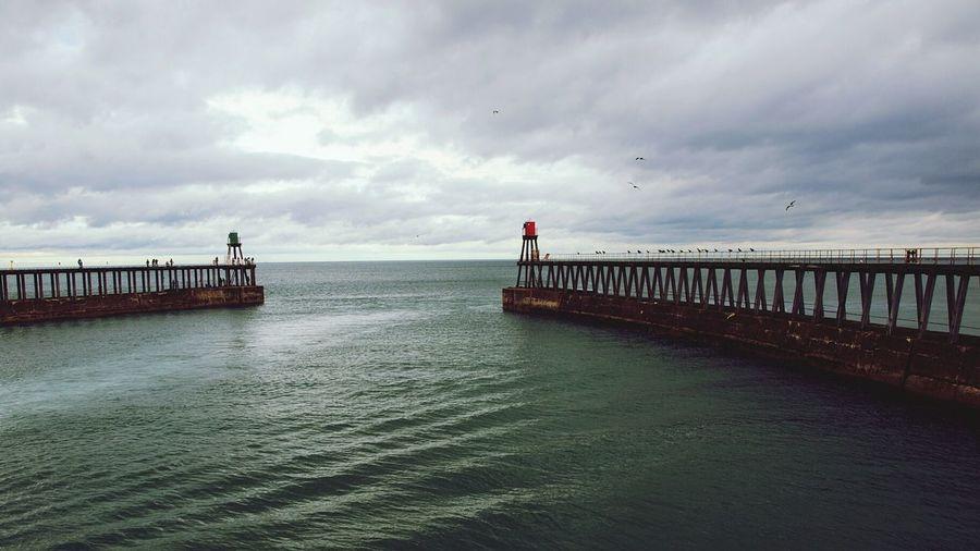 Piers In Sea Against Cloudy Sky