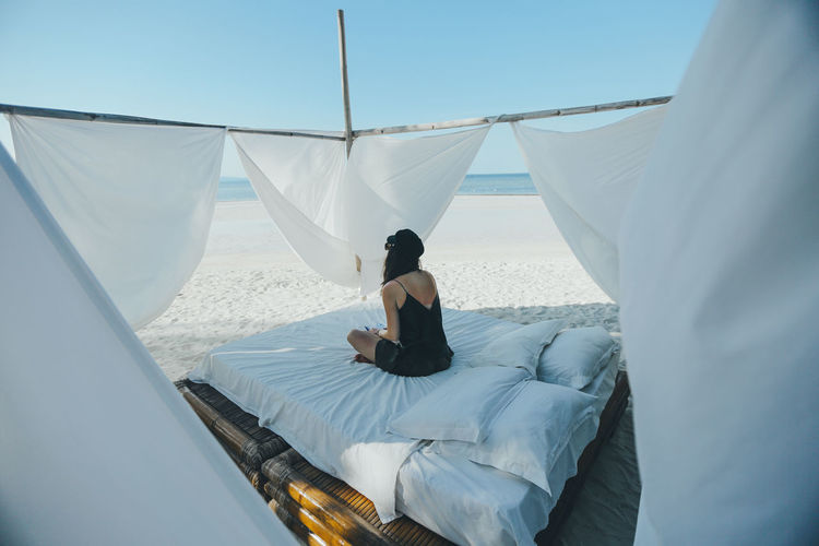 Rear view of woman sitting on bed at beach