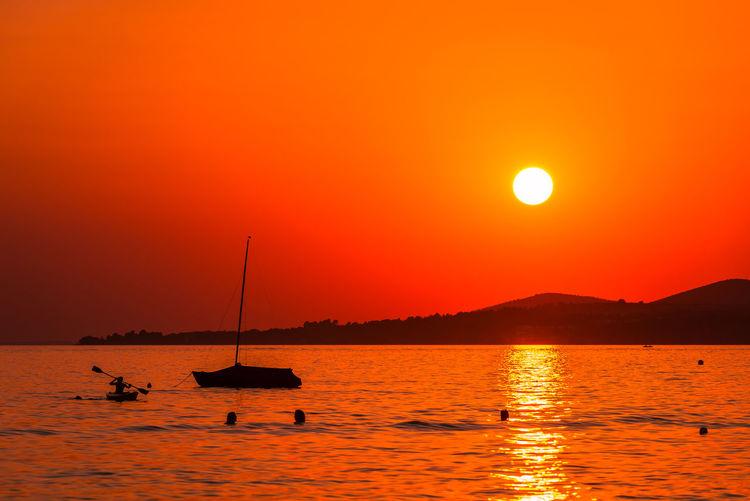 Silhouette sailboats in sea against orange sky