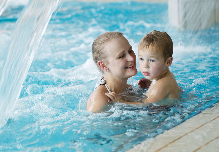 Happy mother with shirtless son in pool at water park