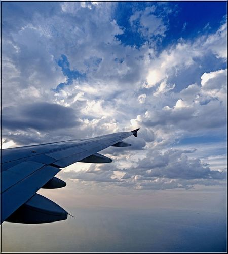 Airplane wing against cloudy sky