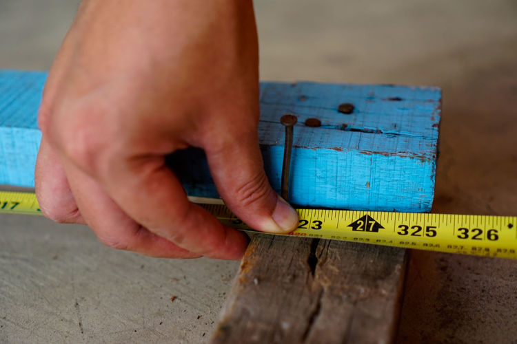 Close-up of cropped hand using tape measure