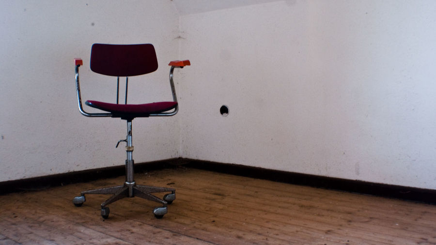Empty office chair against white wall in building