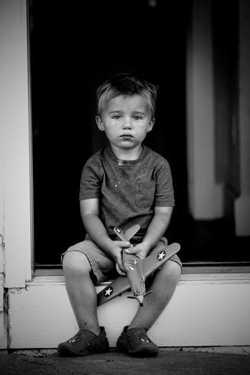 Portrait of cute boy sitting at entrance