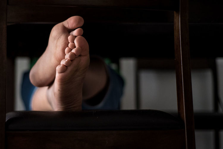 Low section of person with bare feet relaxing on chair