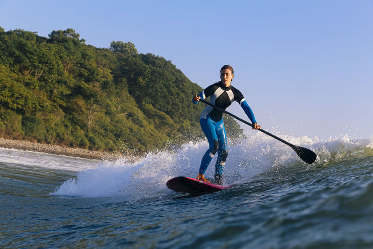 Full length of man surfing in water against clear sky