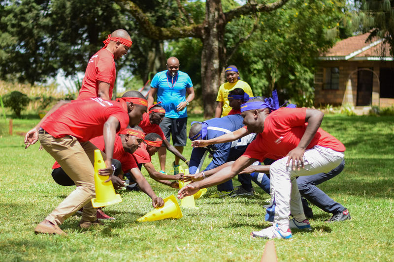 Team building exercise for who was the fastest at picking up the cones Adult Casual Clothing Crouching Day Enjoyment Full Length Fun Grass Group Group Of People Leisure Activity Men Nature Outdoors People Plant Playing Real People Team Building Activity Togetherness Tree