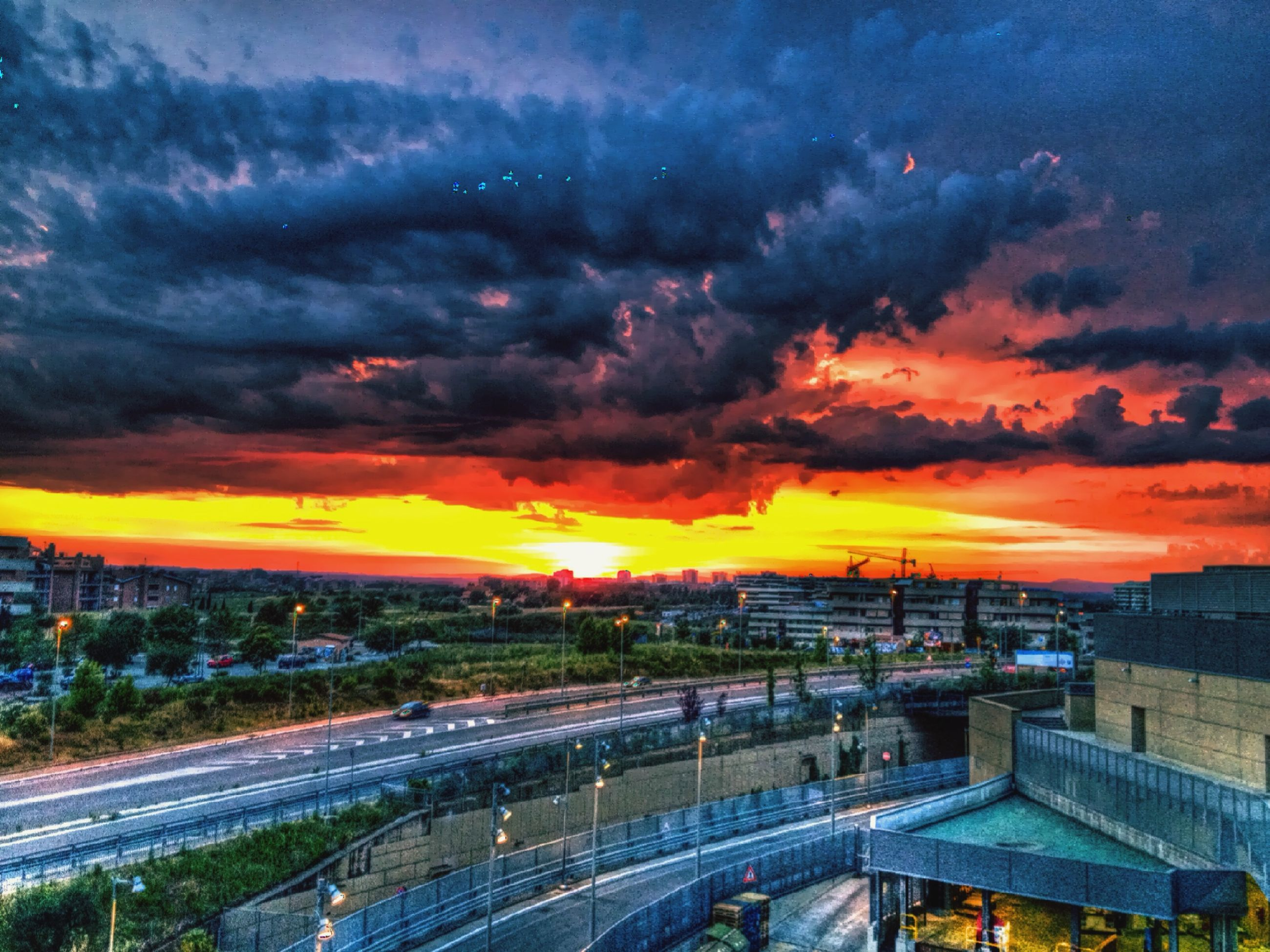 sunset, cloud - sky, sky, orange color, dramatic sky, cloudy, cloud, beauty in nature, scenics, high angle view, nature, landscape, built structure, architecture, moody sky, atmospheric mood, building exterior, weather, outdoors, road