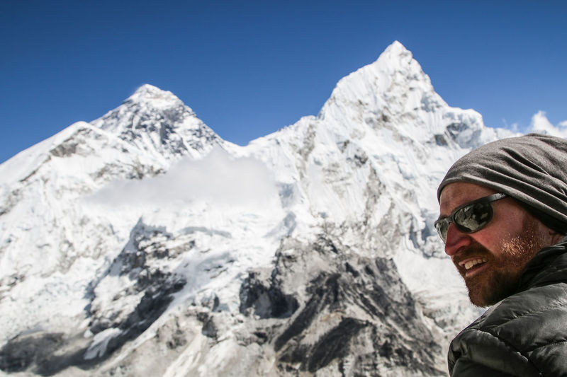 Portrait of man with snowcapped mountains against sky