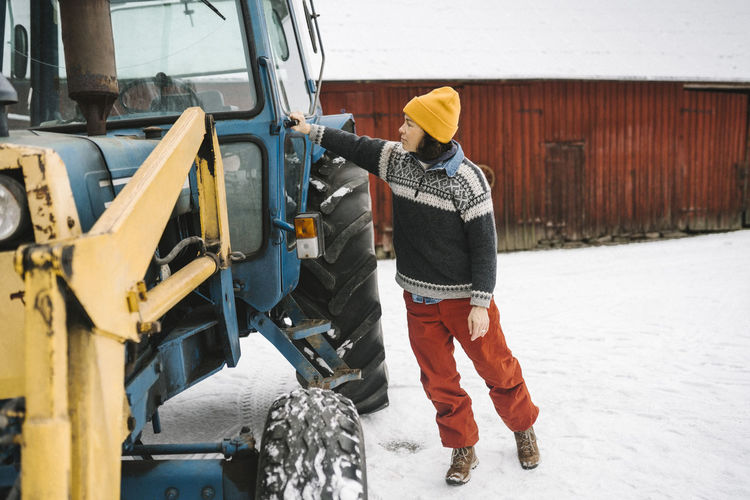 Rear view of man working on snow