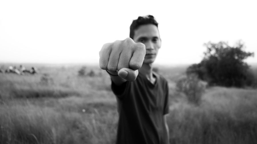 Portrait of young man clenching fist on grassy field against sky