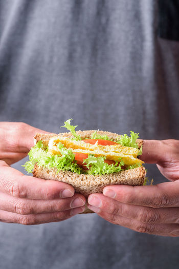Midsection of man having sandwich